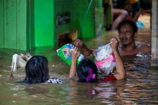 Women carry diapers as they cross a flooded area Jan. 2, 2020, after heavy rains in Jakarta, Indonesia.Caritas Indonesia (Karina) has joined forces with the Jakarta Archdiocese in distributing aid to people hard hit by floods that have killed dozens of people.