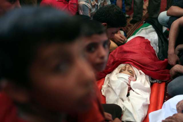 "Palestinians surround the body of a 10-year-old girl, whom hospital officials said was killed in an Israeli airstrike, during her funeral at a mosque in Rafah, in the Gaza Strip, July 11. In response to the ""tragic events"" unfolding in the Middle East, Pope Francis delivered ""a heartfelt appeal to continue to pray with persistence for peace in the Holy Land."""