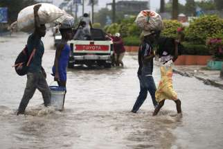 People cross a flooded street in Port-au-Prince, Haiti, Aug. 23, 2020, during the passage of Tropical Storm Laura.