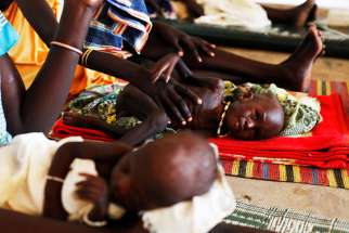 Malnourished children lie next to their mothers July 15, 2014 at the Medecins Sans Frontieres Hospital in Leer, Sudan.