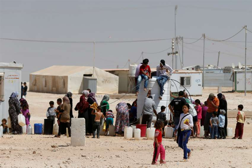 Syrian refugees collect water at the Zaatari refugee camp near Mafraq, Jordan, Aug. 18, 2016.