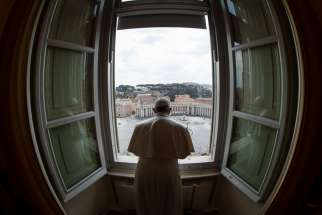Standing in the window of the library of the Apostolic Palace overlooking an empty St. Peter's Square, March 29, 2020, Pope Francis blesses the city of Rome, still under lockdown to prevent the spread of the coronavirus.