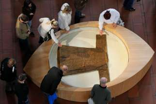 "Pilgrims touch a casing containing the ""'Holy Robe"" in the cathedral in Trier, Germany, April 15. The ancient town of Trier marks the 500th anniversary of the first public appearance of the Seamless Robe of Jesus, reportedly worn during, or shortly before his crucifixion. Some 500,000 pilgrims are expected to visit the relic through May 13."