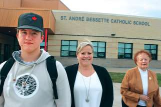 Noah Ethier, his mother Michelle Ethier and grandmother Simone Bessette stand outside the new Fort Saskatchewan school named after their relative, St. André Bessette.