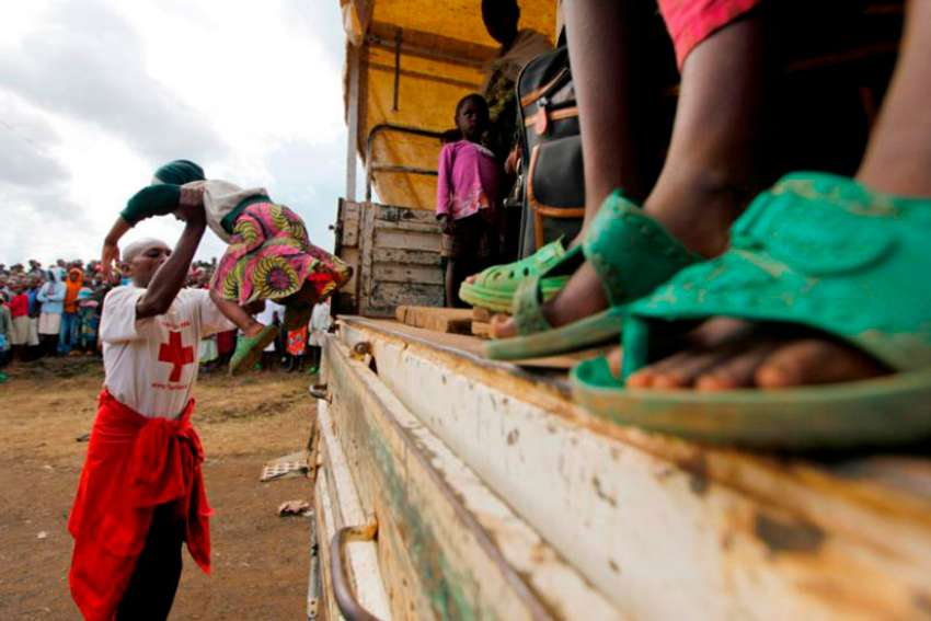 A Congolese refugee girl is helped off a truck near the border town of Gisenyi, Rwanda, in this 2012 file photo. Armed men kidnapped two Catholic priests in the troubled North Kivu province July 16.