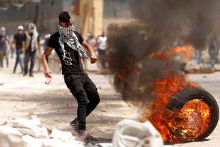 A Palestinian protester in Beita, West Bank, moves a burning tire during clashes with Israeli troops April 28. Catholic leaders in the Holy Land urged Israel to concede to demands of Palestinian political prisoners on a hunger strike since April 17.