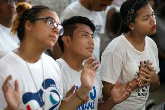 Yassiel Barranco, 21, Ivan Lopez, 20, and Liz Marie, 17, pray during a vigil for young people at the Church of Christ the Redeemer April 22 outside Panama City. World Youth Day 2019 will be celebrated Jan. 22-27 in Panama City.