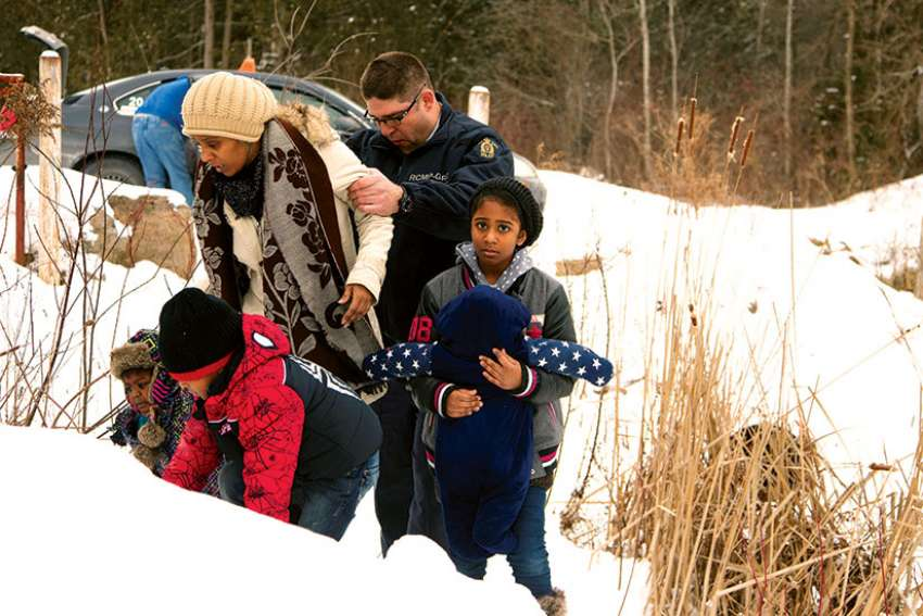 A woman and her family from Sudan is taken into custody by a Royal Canadian Mounted Police officer after arriving Feb.12 by taxi and walking across the U.S.-Canada border into Quebec.