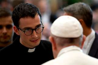 Pope Francis greets a participant during a meeting with seminarians from Italy's Lombardy region at the Vatican Oct. 13.