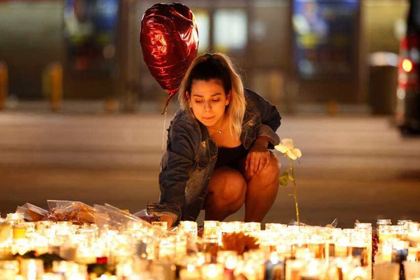 A woman lights candles at a makeshift vigil on the Las Vegas Strip Oct. 2 following a mass shooting at an outdoor country music festival. Late Oct. 1 a gunman perched in a room on the 32nd floor of a casino hotel unleashed a shower of bullets on the festival below, killing at least 59 people and wounding another 527. Three Canadians are among the dead.