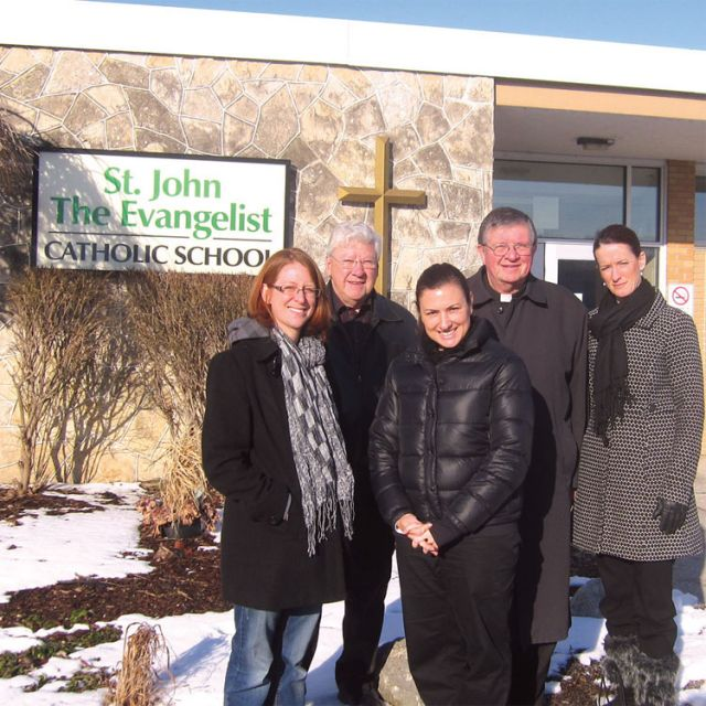 Woodslee community association members Jennifer Levack and Paul Mullins stand with local chair of the Catholic School Council Melissa Tavolieri, Fr. Dave Boutette and principal of St. John the Evangelist Catholic School Pam Prsa (left to right) outside of the school they seek to save.