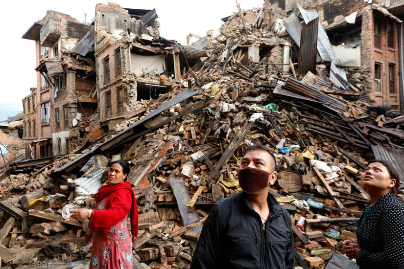 Survivors look at destroyed buildings April 27 following an earthquake in Bhaktapur, Nepal. More than 3,600 people were known to have been killed and more than 6,500 others injured after a magnitude-7.8 earthquake hit a mountainous region near Kathmandu April 25.