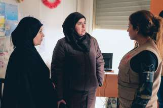 Pierrette Gabriel, right, a receptionist at the Caritas Lebanon center in Zahle, greets two Syrian refugee women seeking assistance for their families Jan. 4.