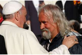 Pope Francis greets one of eight poor people at his general audience in St. Peter's Square at the Vatican Dec. 17, the pope's 78th birthday. A group of the poor were invited to the audience in celebration of the pope's birthday.