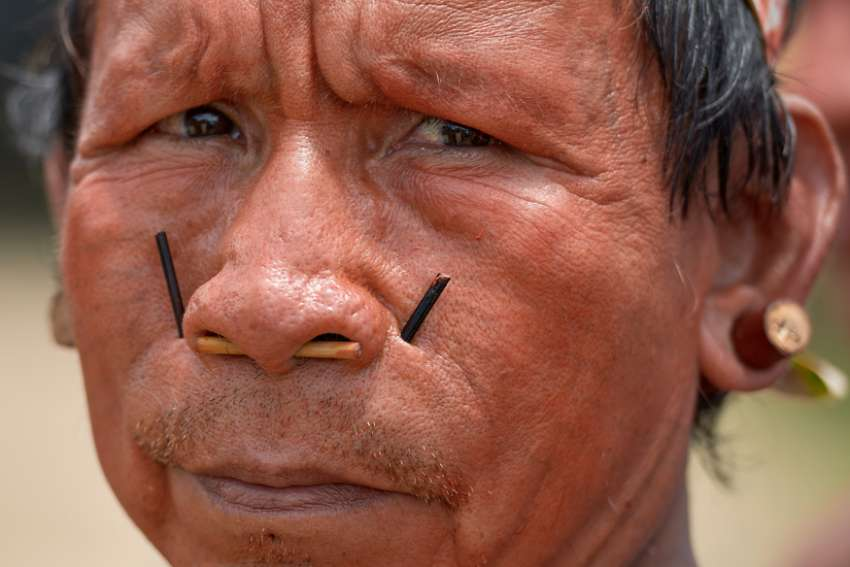His face painted red with urucum, a man participates in a march by indigenous people through the streets of Atalaia do Norte in Brazil's Amazon region March 27, 2019. Existing formation programs are not preparing priests and other pastoral workers to be leaders in a church with an Amazonian and indigenous face, according to bishops participating in the Synod of Bishops for the Amazon.