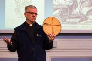 Fr. John McCarthy, in his lecture at Regis College March 21, displays a tree core sample he found in New Brunswick that handily demonstrates the Jesuit principle of finding God in all things. McCarthy is a lichenologist and ecologist who also is chaplain at the University of British Columbia.