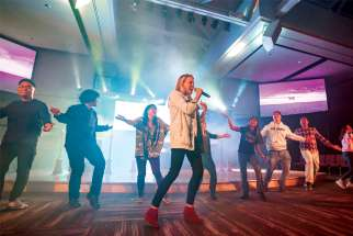 Catholic speaker and musician Emily Wilson is joined on stage by young adults at the One Rock 2.0 conference in Calgary.