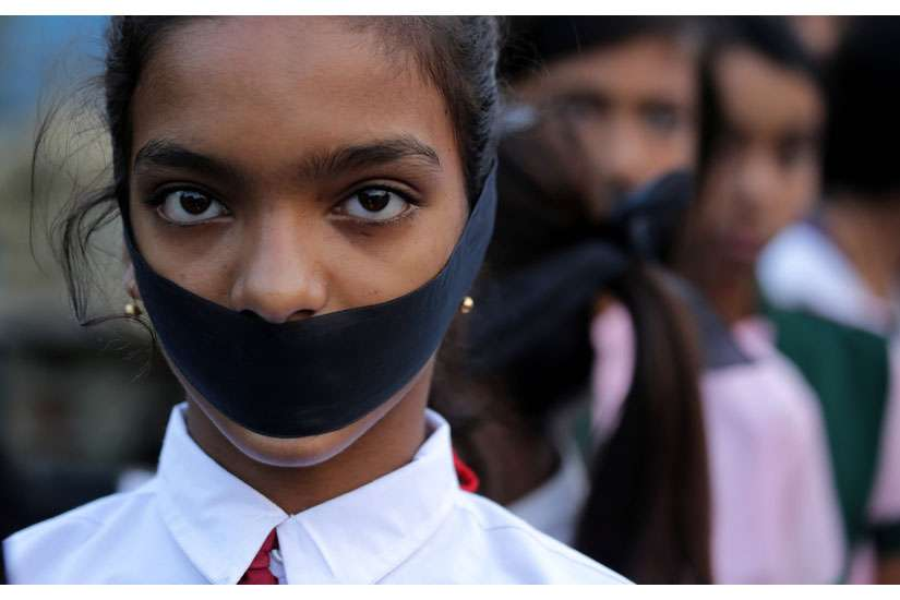 A student tapes her mouth shut during a March 16 candlelight vigil for an elderly nun who was raped in Ranaghat, India.