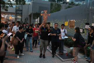 About 100 Catholic youths pray for democracy outside Hong Kong's government headquarters building Sept. 30. Two cardinals in Hong Kong urged the government to solve the present political deadlock after police used force to disperse thousands of unarmed p rotesters who struggled for full democracy in the city.