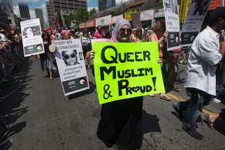 "A woman carrying a sign that reads, ""Queer, Muslim and Proud"" marches during the Gay Pride parade in Toronto on July 1, 2012."