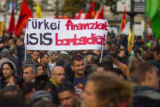 People hold a banner during an Oct. 12 demonstration in Berlin against the Islamic State militant group, known as ISIS, and its insurgent attacks on the Syrian Kurdish town of Kobani.
