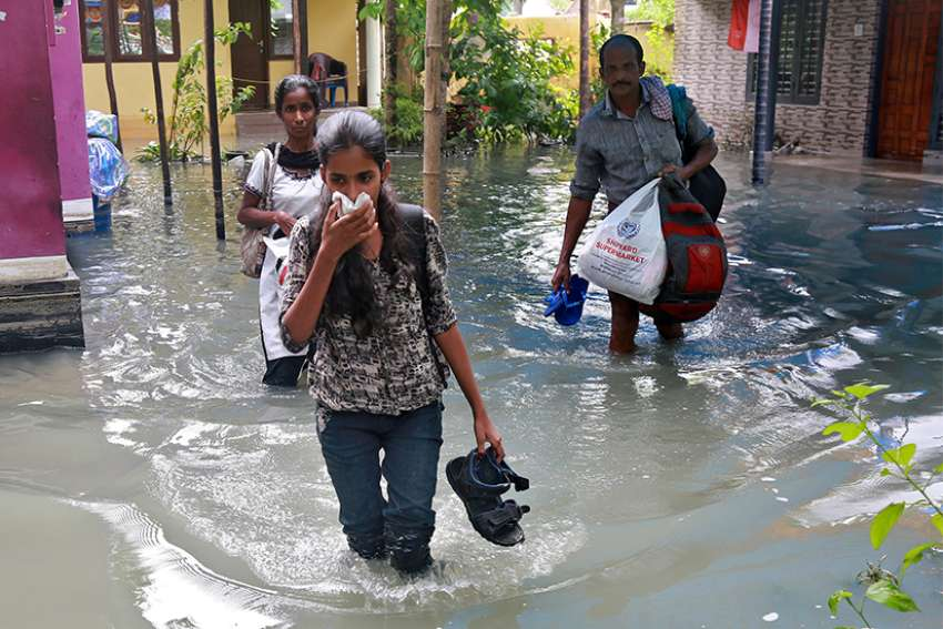 Residents carry their belongings as they evacuate their home Dec. 2 after flooding caused by Typhoon Ockhi in the coastal village of Chellanam in the southern state of Kerala, India. The storm claimed the lives of at least 32 poor Catholic fishermen who were at sea and 200 more were missing.