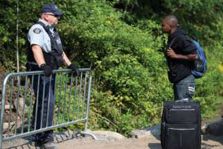 A Haitian man talks with an RCMP officer as he waits to cross the U.S.-Canada border into Quebec last summer.