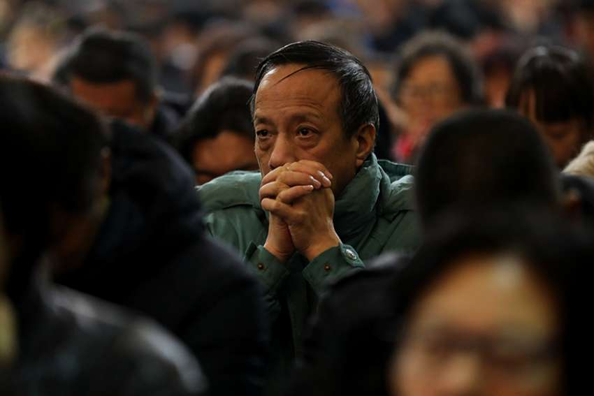 A man prays during Mass in 2017 at in the Church of the Immaculate Conception in Beijing. Sources say a long-awaited Vatican agreement with China, expected to be signed soon, only solves some of the issues of the church in China.