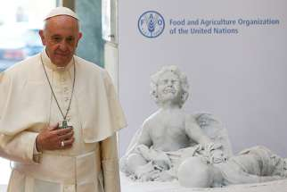Pope Francis presents the U.N. Food and Agricultural Organization with a marble statue during his visit to FAO headquarters Oct. 16. It is a statue of Alan Kurdi, the 3-year-old Syrian boy who drowned during a Mediterranean crossing in September 2015.
