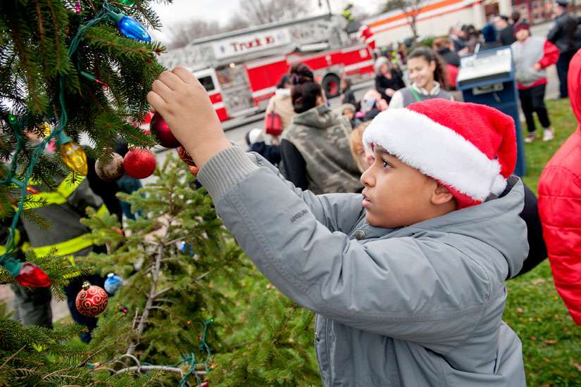 Johnnavin Rodriguez, 11, decorates a Christmas tree outside St. Michael Church in Rochester, N.Y., Dec. 16.