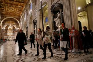 Cardinal Kevin Farrell, prefect of the Dicastery for Laity, the Family and Life, walks behind youths attending a pre-synod meeting as they participate in the Way of the Cross at the Basilica of St. John Lateran in Rome March 23. The meeting is being held in preparation for the Synod of Bishops on young people, the faith and vocational discernment this October at the Vatican