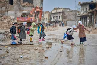 Girls navigate a muddy street Dec. 5 as they make their way to school amid the rubble of the Old City of Mosul, Iraq. when Islamic State controlled the city,most children did not attend school.