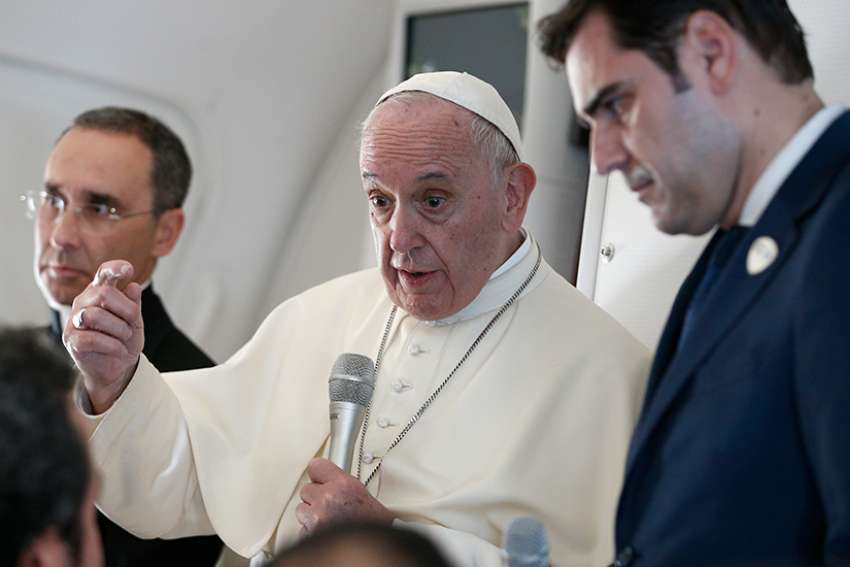 Pope Francis answers questions from journalists aboard his flight from Abu Dhabi, United Arab Emirates, to Rome Feb. 5, 2019. Also pictured are Msgr. Mauricio Rueda, papal trip planner, and Alessandro Gisotti, interim Vatican spokesman.