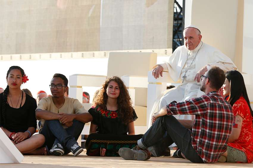 In this 2016 file photo, World Youth Day pilgrims sit in front of Pope Francis at the Field of Mercy in Krakow, Poland.