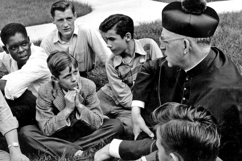 Fr. Edward Flanagan talks with a group of boys in this undated photo.