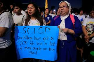 "A young woman displays a placard as a nun prays the rosary Feb. 24 during a protest against plans to reimpose the death penalty and intensify the drug war during a ""Walk for Life"" rally at a park in Manila, Philippines."