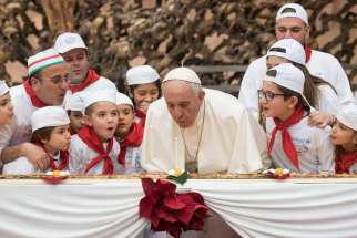 Pope Francis blows a candle on his four-metre long pizza surrounded by his special guests pizza at St. Peter's Square Dec. 17.