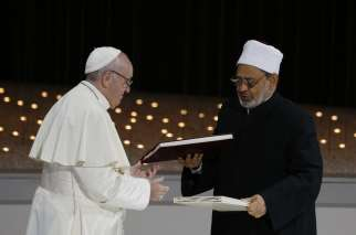 Pope Francis and Sheik Ahmad el-Tayeb, grand imam of Egypt's al-Azhar mosque and university, exchange documents during an inter-religious meeting at the Founder's Memorial in Abu Dhabi, United Arab Emirates, Feb. 4.