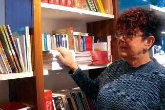 Manager Shirley Kulmatycki scans some of the packed shelves in the Newman Theological College Bookstore in Edmonton.