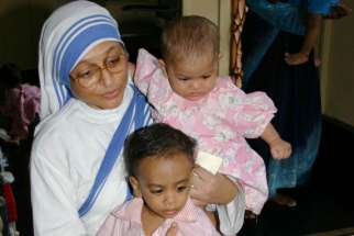 A member of the Missionaries of Charity holds orphan children in 2007 at a center in Kolkata, India. The Missionaries of Charity will close their adoption centers in India, citing new regulations that would allow nontraditional families to adopt children, reported ucanews.com.