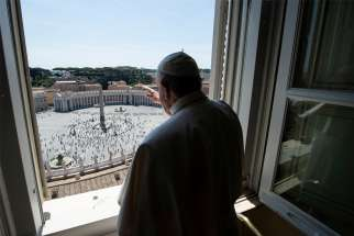 "Pope Francis waves as he looks out on St. Peter's Square after leading the ""Regina Coeli"" from his library in the Apostolic Palace at the Vatican May 24, 2020. It was the first time the public was allowed in the square given the ongoing easing of restrictions during the coronavirus pandemic."