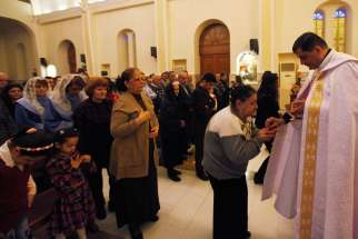 A priest gives Communion during Mass at a church in Baghdad March 1. Christian organizations have begun funneling aid to Syrian cities that are housing refugees from the Islamic State.