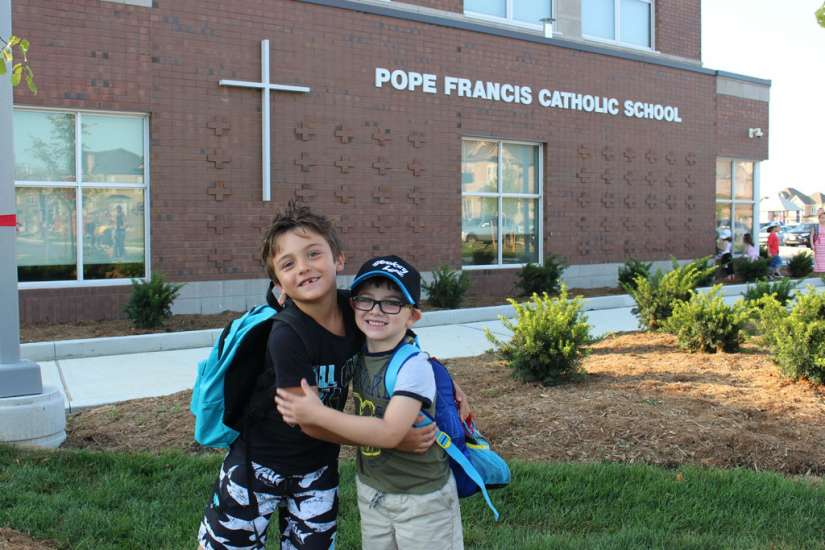 Children posing in front of the newly built Pope Francis Catholic School in York Region