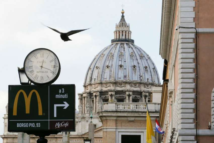 A sign in front of St. Peter's Basilica points to the newest McDonald's restaurant in Rome, next to the Vatican. Jan. 3, 2017.