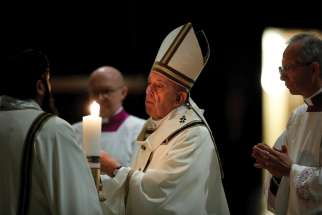 Pope Francis lights the paschal candle at the start of the Easter Vigil in St. Peter's Basilica April 11, 2020.