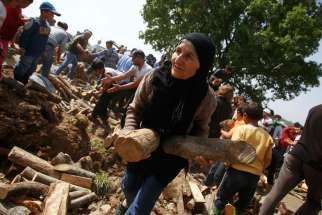 A woman holds firewood distributed near a makeshift camp for migrants April 14 at the Greek-Macedonian border near the village of Idomeni, Greece. A Vatican spokesman said Pope Francis' April 16 trip to Greece is humanitarian, not political.