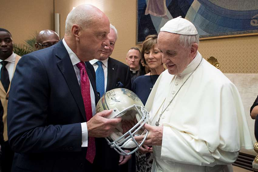 Pope Francis is presented with an American football helmet during a meeting with members of American Pro Football Hall of Fame June 2017 at the Vatican.