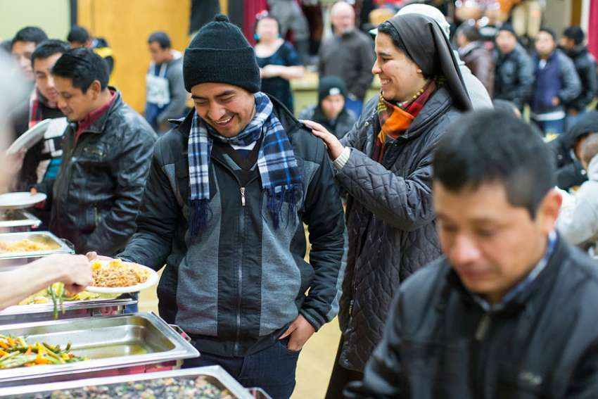 A nun shares a light moment with a man during a meal following a Dec. 17 Mass for migrant workers at Our Lady of Sorrows Church in Vancouver, British Columbia.
