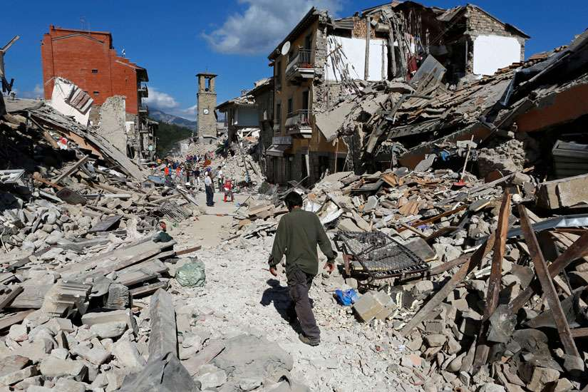 A man walks amidst rubble following an earthquake in Pescara del Tronto, central Italy, August 24, 2016.