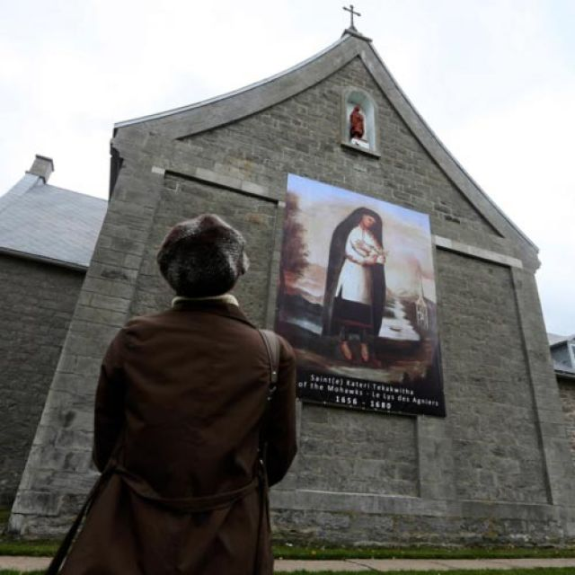 "A woman looks at a banner of St. Kateri Tekakwitha displayed outside St. Francis Xavier Church, where she is buried, in Kahnawake, Quebec, Oct. 21. Pope Benedict XVI created seven new saints that day, including St. Kateri, a 16th-century Mohawk-Algonquin woman known as the ""Lily of the Mohawks."""